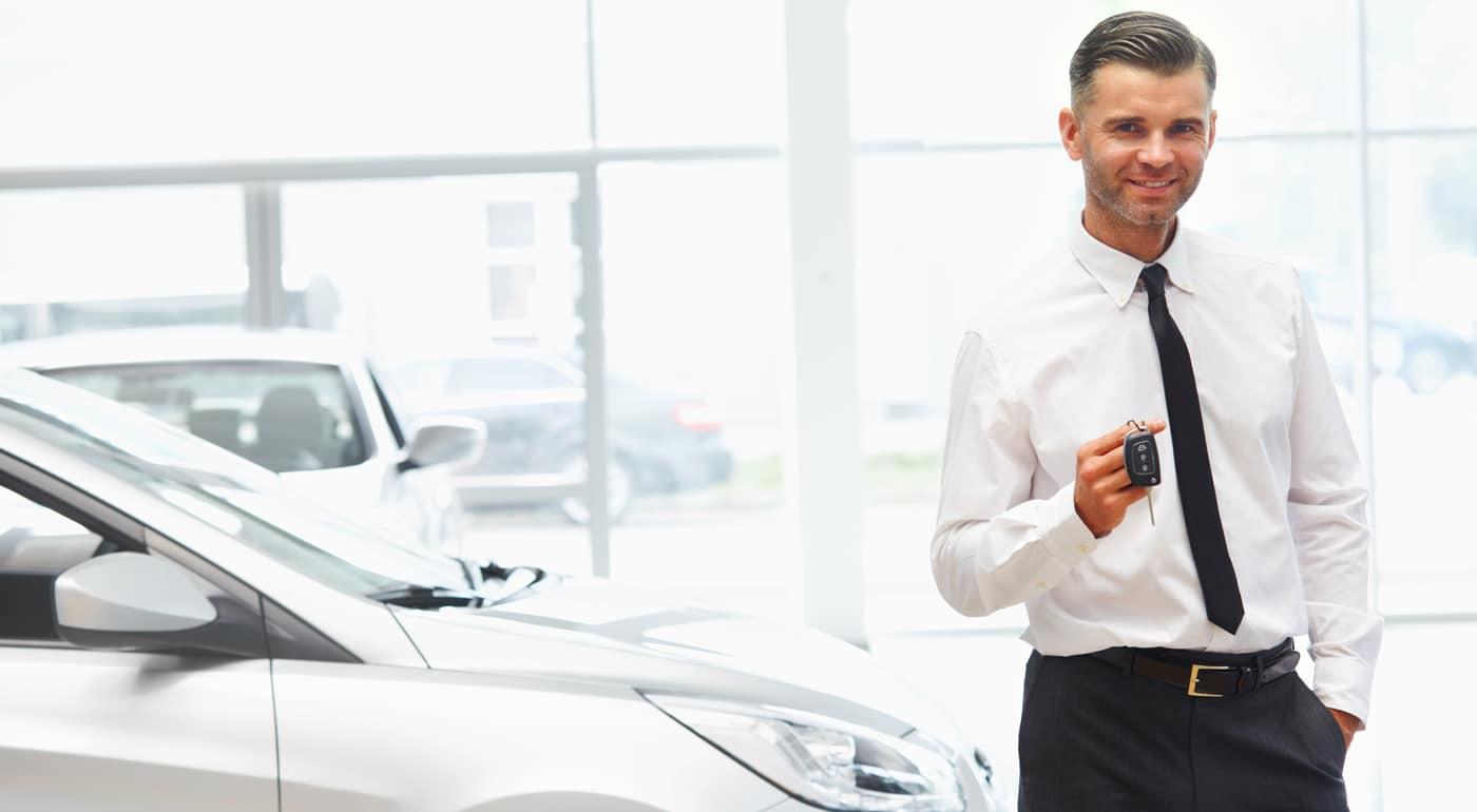 Un mandataire auto devant des voitures neuves