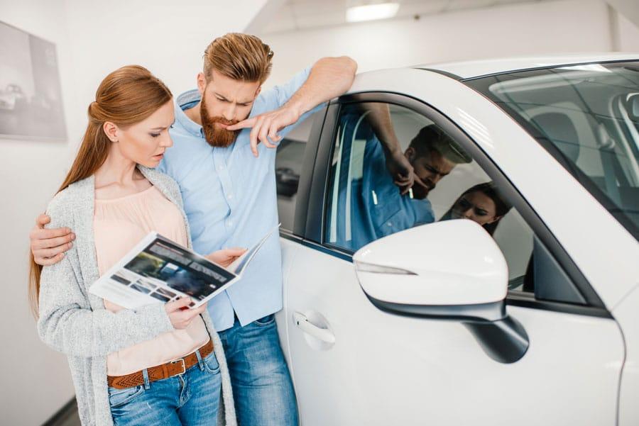 Des personnes chez un professionnel automobile, pour acheter une voiture d'occasion