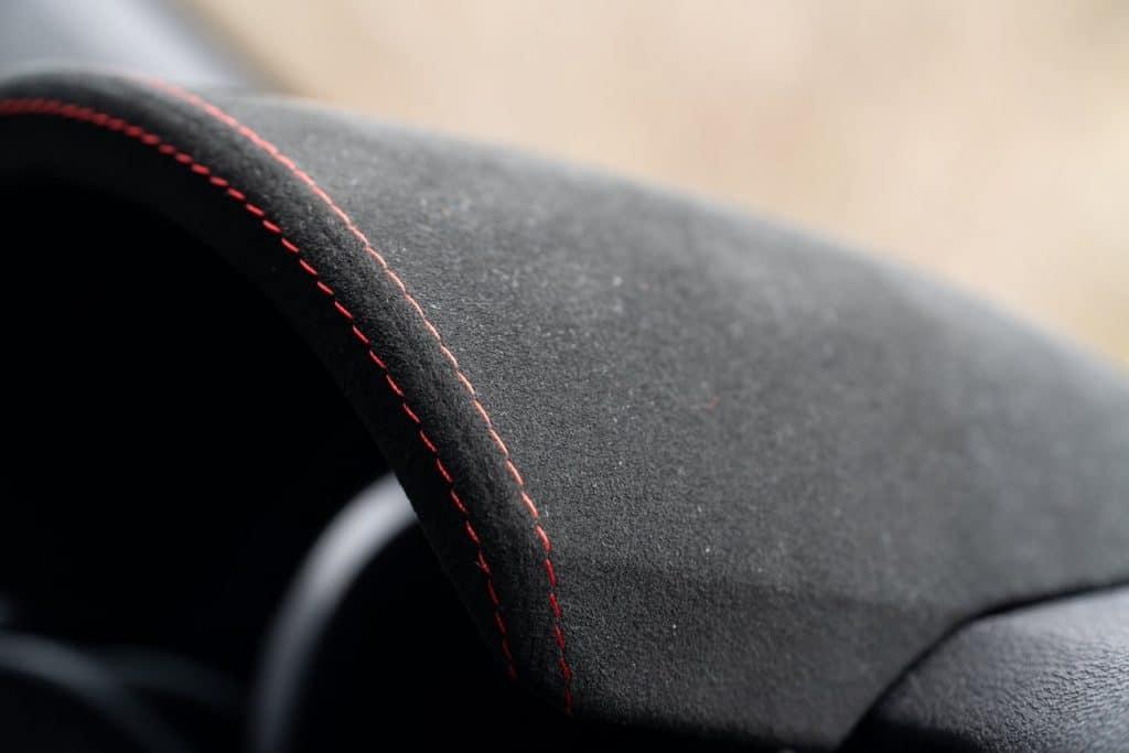 La planche de bord du Fiat 500x est recouverte d'Alcantara avec surpiqure rouge