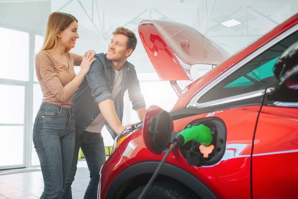 Un couple qui vient d'acheter une voiture hybride