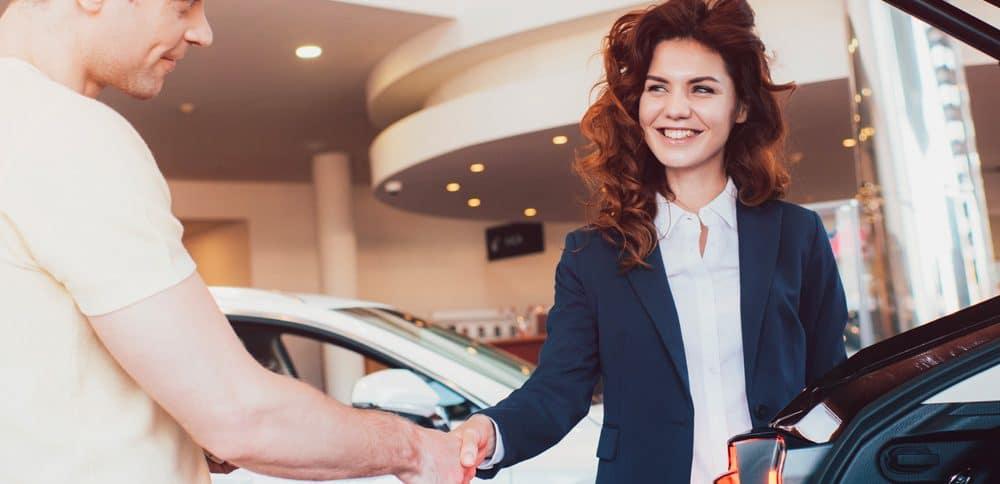 Une dame serre la main d'un vendeur dans une concession automobile.