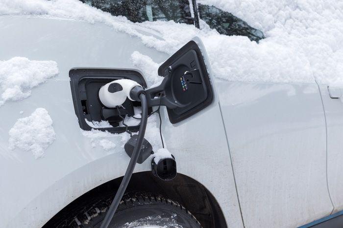 Voiture électrique couverte de neige en train de charger