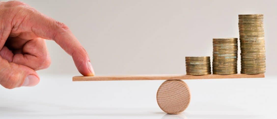 Doigt qui appuie sur une balance avec des pièces de l'autre côté.