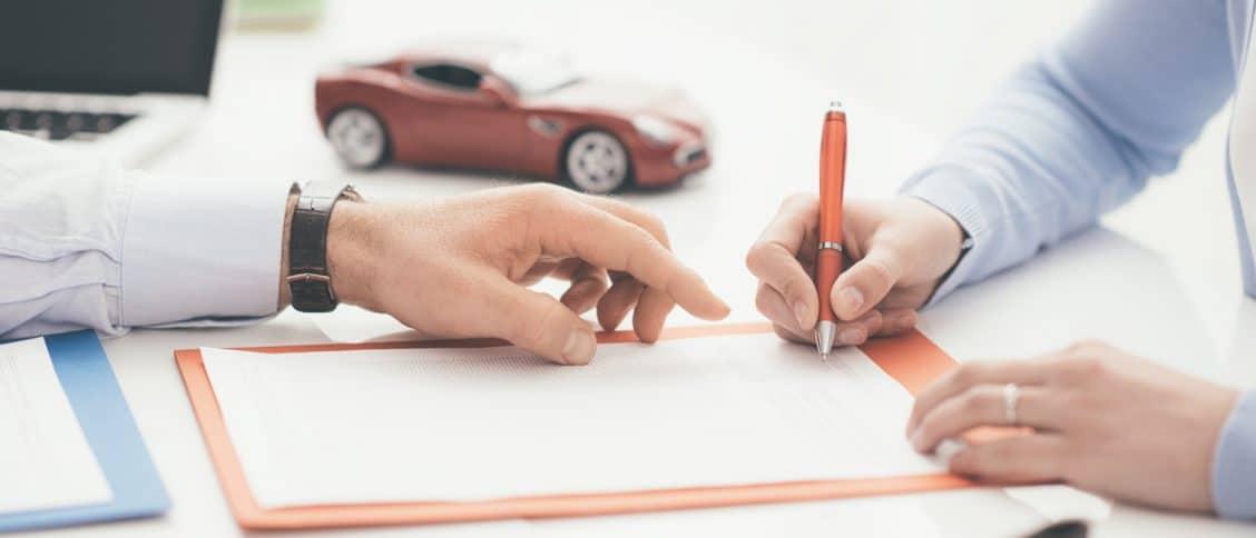 Une personne en train de signer un contrat pour une nouvelle voiture