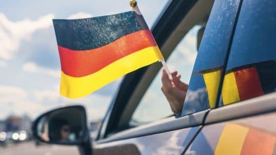 Personne qui tient un drapeau allemand dans une voiture